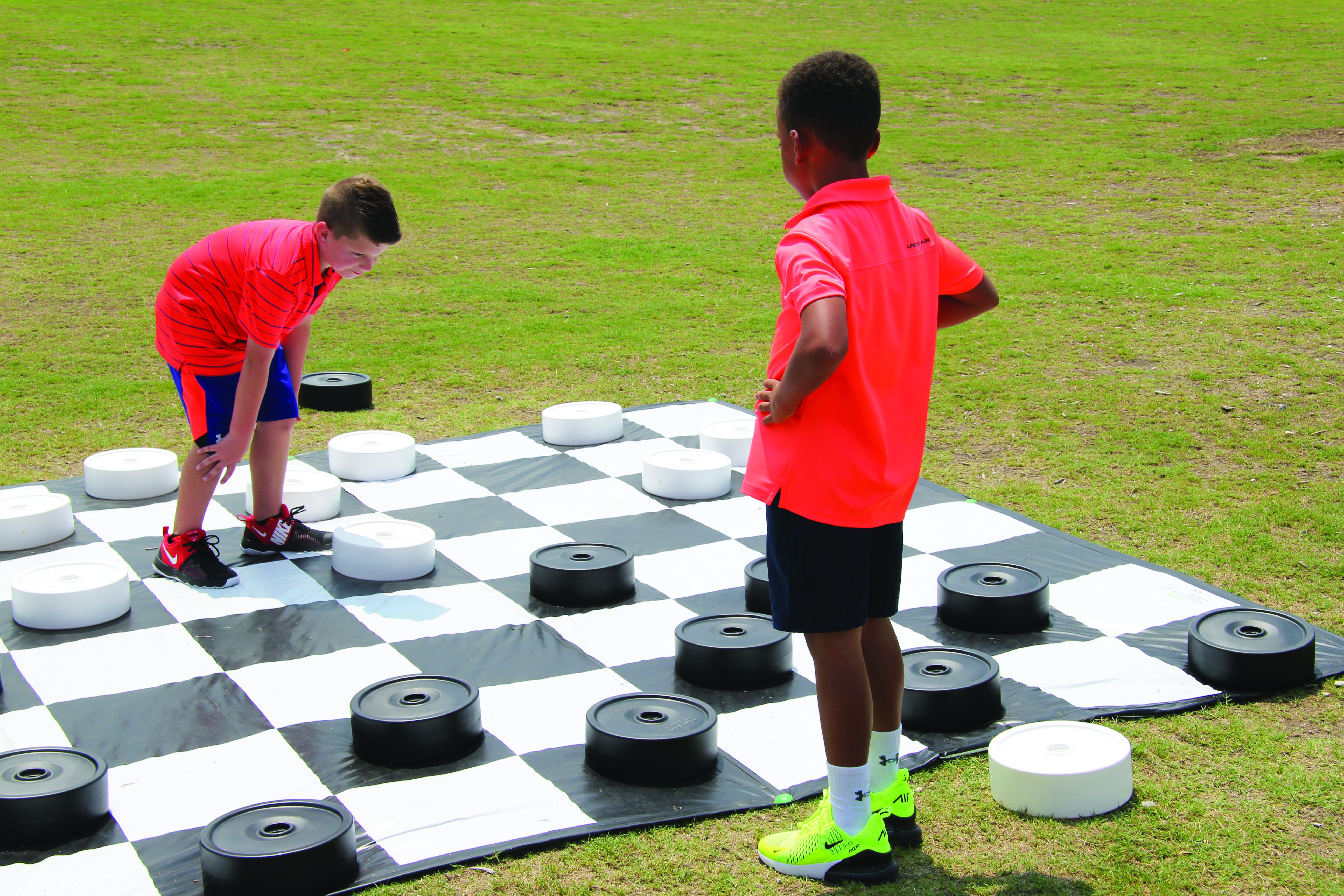 kids taking a brain break to play checkers outside
