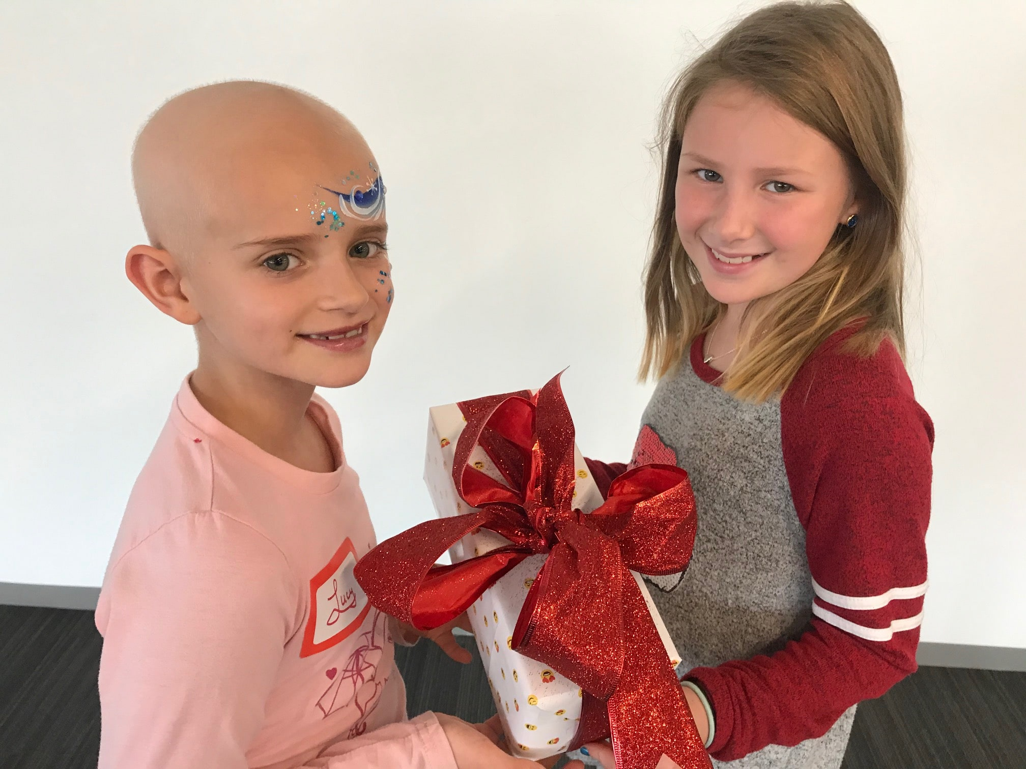 Kate Trizila giving a gift to a Heroes for Children recipient
