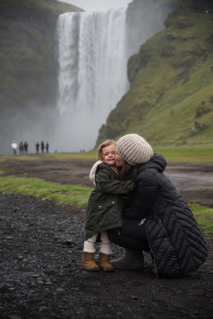 Mother and daughter at waterfall on family trip to Iceland