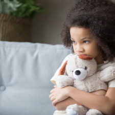 Stressed child holding teddy bear