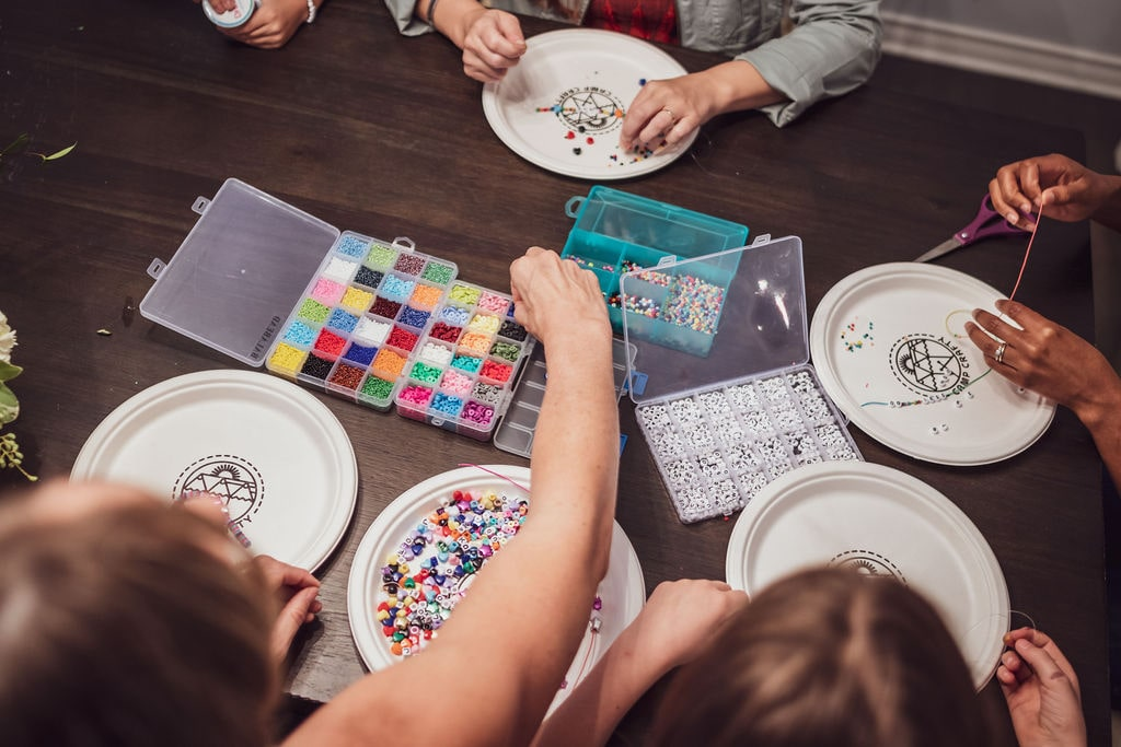 People at table grabbing beads; How to throw an arts and crafts party