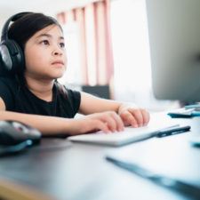 Young girl doing homework on computer; aware of cyber security