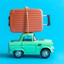 Car with suitcase on top; travel tips and tricks for families