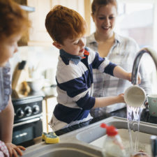 Kids doing chores in the kitchen; washing dishes