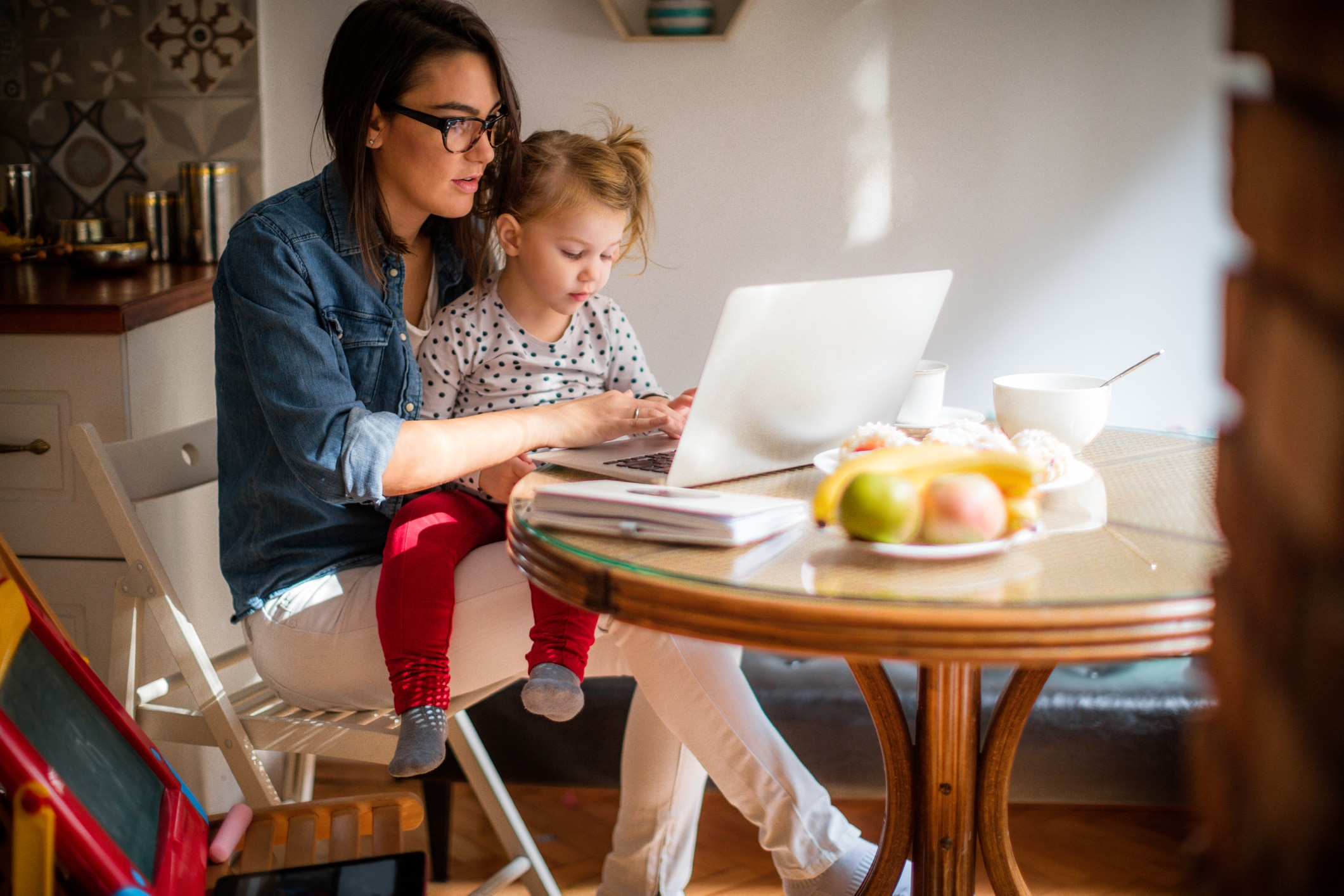 Work at home mom with daughter on lap