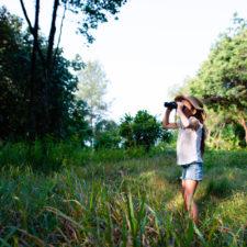 Little girl using binoculars learning about birds