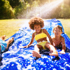 Kids on waterslide in the backyard during summer