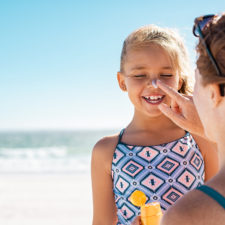 Mom applying sunscreen to daughter's face