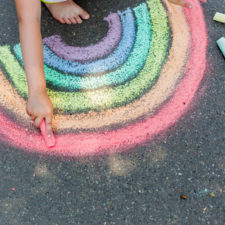 Girl drawing with chalk in the summer