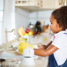 Little girl washing dishes in the kitchen learning life skills
