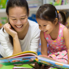 Mom and daughter reading books about big kid beds