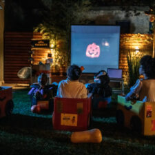 family watching Halloween movies in the backyard, iStock