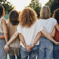 women friends holding hands, postpartum depression, iStock