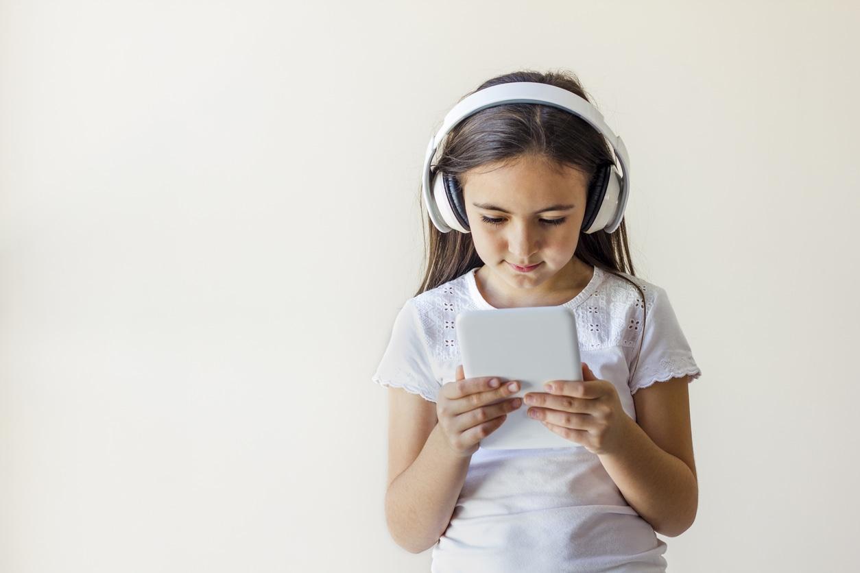 little girl using apps on tablet