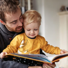 little boy reading books with his dad