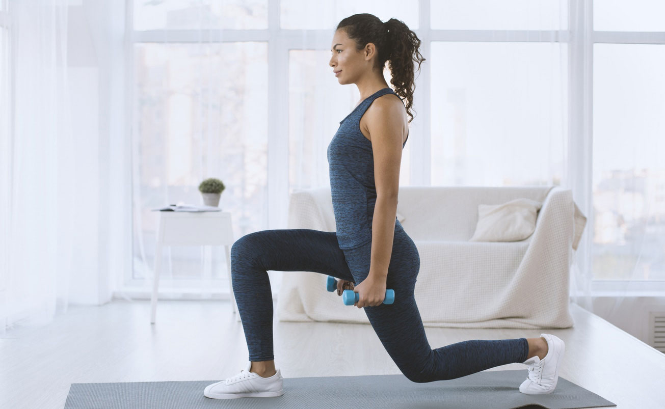 lunges with dumbbells at home, fitness apps, iStock